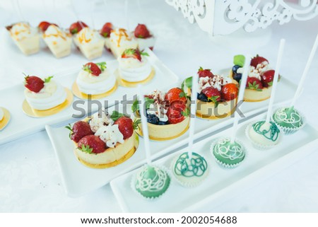 Candy bar. White festive table with deserts, strawberry tartlet and cupcakes. Wedding. Reception Tartlets