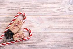 candy canes and christmas gift on brown wooden rustic vintage background.