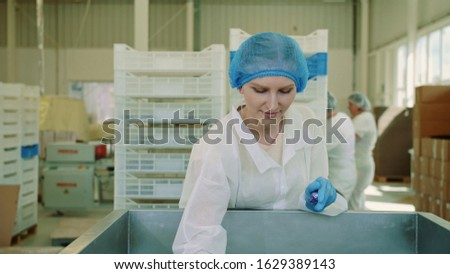 Candy factory. Factory worker checking packing machine. Young woman in uniform inspecting packing machine while working in confectionery factory.