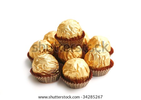 candy in golden foil over white background