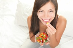 Candy woman eating sweets with a fresh smile in bed - copy space. Top view of Mixed Chinese Asian / Caucasian young female model.