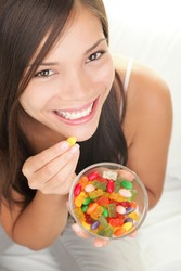Candy woman. Girl eating winegum gummy bears and other sweets smiling looking at camera.