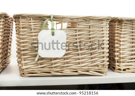cane baskets on a shelf, white background and blank label/card with ribbon
