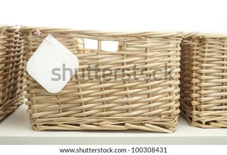 cane storage basket with blank tag - stock photo