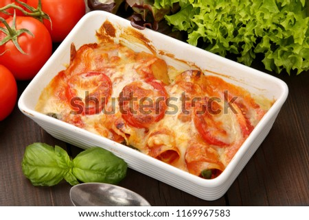 Caneloni stuffed with meat and melted cheese in white bowl over grunge wood background