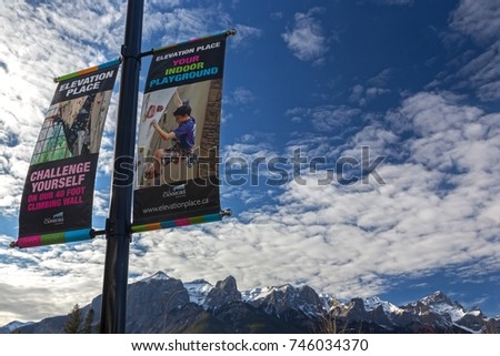 CANMORE, ALBERTA, CANADA - OCTOBER 30, 2017: Promotional Flags and Distant Rocky Mountains Background in front of Elevation Place Recreational Facility