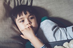 Canndid shot of kid lying on safa biting his finger nails while watching TV, Child boy bite his nails, Emotional child portrait, indoor closeup face