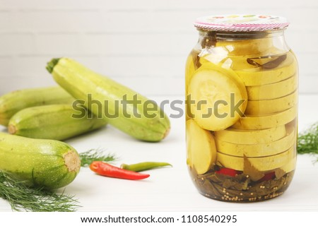 Canned courgettes in a jar, located on a white background. In the background, courgettes are laid out.