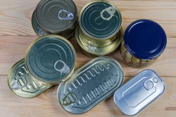 Canned fish and seafood in various types of sealed tin cans and glass jar on a rustic table, top view
