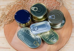 Canned fish and seafood in various types of sealed tin cans and glass jar on a wooden surface with fishing net