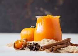 Canned organic pumpkin puree in glass jar with fresh pumpkin, cinnamon and anise on light background. Ingredient for Thanksgiving, autumn or winter recipes.