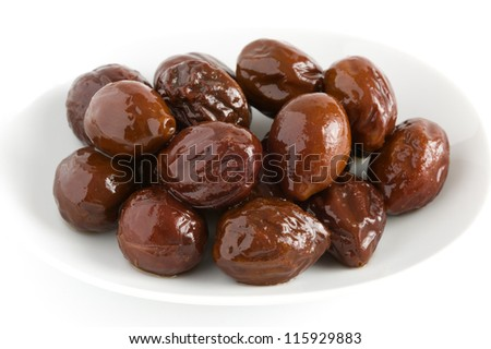 canned prunes on a white dish isolated