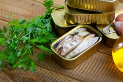 Canned seafood, headless mackerel fish preserved in oil on wooden table