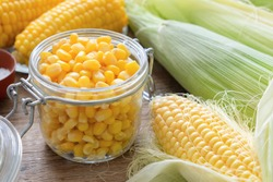 Canned sweet corn in glass jar, fresh and cooked corn on cobs.
