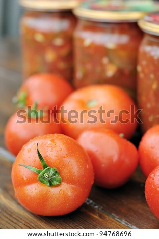 Canned tomatoes. Ripe tomatoes and jars with the tomatoes.