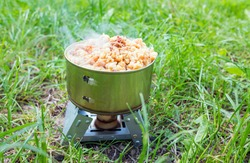 Canned tourist food on a small stove with dry fuel on a camping trip, hiking food concept.