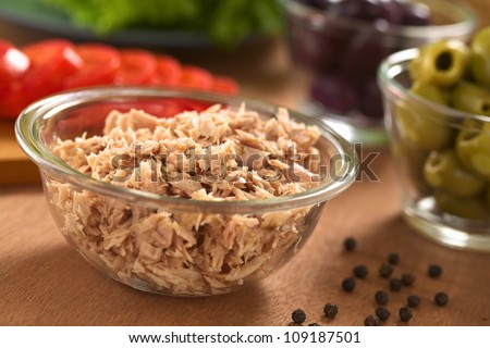 Canned tuna in glass bowl with fresh salad ingredients (olives, tomato, lettuce) in the back (Selective Focus, Focus one third into the tuna)