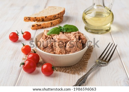 Canned tuna meat in a bowl, fork, bread and fresh red cherry tomatoes on a white wooden table. Low calories healthy eating snack of preserved tuna fish and vegetables. Tasty seafood. Front view.