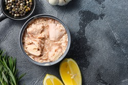 canned tuna open can with fresh herbs garlic and lemon ingredients for preservs top view close up space for text.