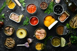 Canned vegetables, beans, fish and fruits in tin cans on black stone background. Food stocks.
