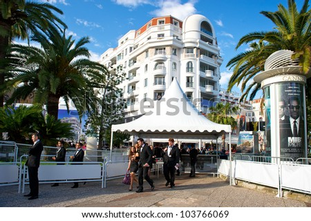 CANNES, FRANCE - MAY 23: Guests walk to the 'Cosmopolis' premiere during the 65th Annual Cannes Film Festival at Palais des Festivals on May 23, 2012 in Cannes, France - stock photo