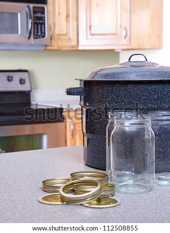 Canning jars with lids, canner or pot in a kitchen setting - stock photo