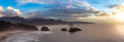 Cannon Beach, Oregon, United States. Beautiful Aerial Panoramic View of the Rocky Pacific Ocean Coast. Dramatic Colorful Sunset Sky.