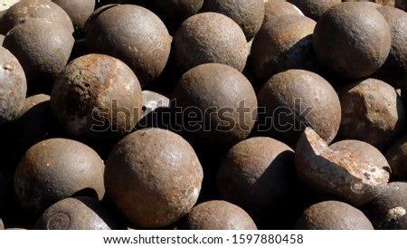 Photo of  cannonballs stacked in a pile of one caliber for firing smoothbore cannons to destroy wooden hulls of ships and fortress, 18th century, Al Fahidi Historical, Dubai.