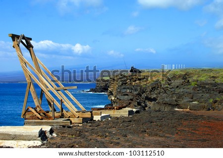Canoe hoist sits on cliffs edge at South Point on the Big Island of Hawaii.  Camper's tent and fishing poles can be seen in background.  Aqua water and blue sky add color to landscape.