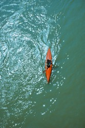 Canoe on a river / A man during sport training on a green river, view from the top