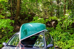 Canoe on car roof in front of a northern forest with bright green maple leaves and granite boulders.
