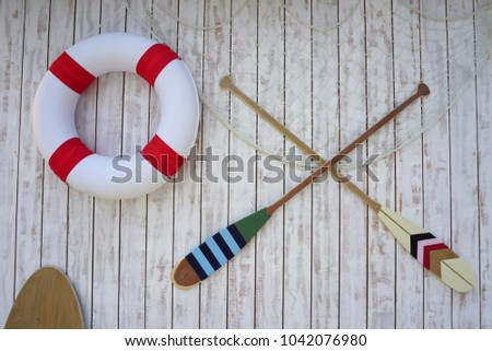 Canoe paddles and lifebuoy hanging on the wall. #1042076980