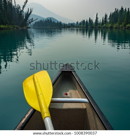 Canoe prow and yellow paddle on the still waters of the Bow River, Banff. Mountains and forests frame the background. #1008390037