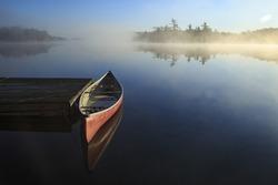 Canoe reflected in the still lake