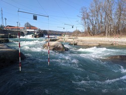 Canoe slalom gates on white water river course in Tacen, Slovenia. Canoe and kayak training and competition facilities on a fast flowing river