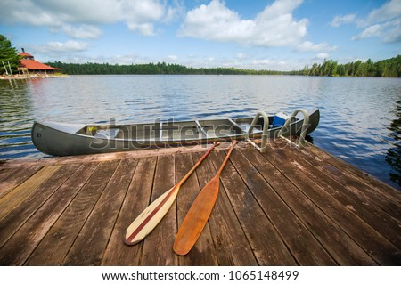 Canoe tied to a wooden dock on a summer day. On the dock there are two paddles. There's a fishing rod inside the canoe.