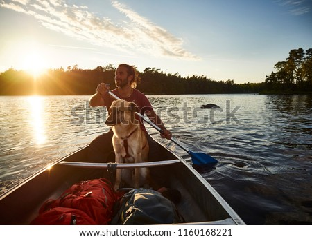 Canoe tour with a dog and a man in sweden #1160168221