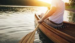 Canoeing. Close up of man holding canoe paddle at sunset lake