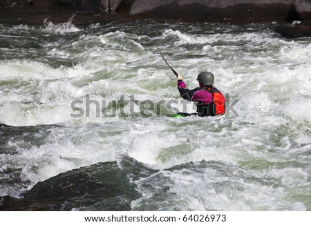 Canoeing in white water in rapids on river with the kayak starting to sink in the waves