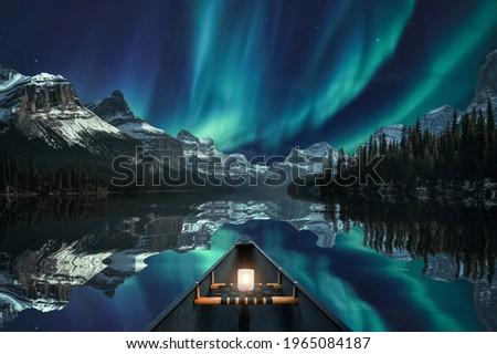 Canoeing with Aurora Borealis over mountain range in Maligne Lake at Jasper national park, Canada. Fine art concept Stock photo ©