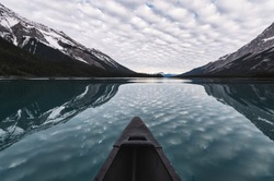 Canoeing with cloudy reflection on Maligne Lake in Rocky Mountains at Jasper national park, Canada