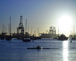 Canoeist crossing the bay at sunrise, anchored sailboats and port in the background, Las Palmas of Gran Canaria