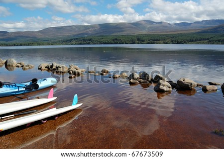 canoes at the edge of loch morlich in the highlands of scotland