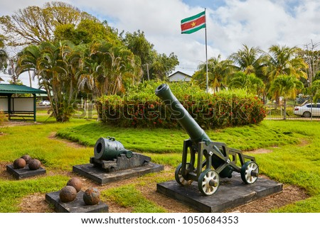 Canons and canon balls with the flag of Suriname in Fort New Amsterdam (1734) on the riverbank where the Commewijne River and Suriname River meet, near Paramaribo, Suriname, South-America #1050684353