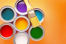 Cans of paints and brush on color background