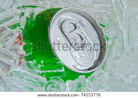 Cans of soft drink, cooling frozen and with water drops in ice background
