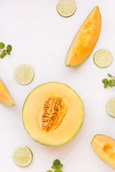 Cantaloupe melon half and slices and lime on white background. Top view, copy space, flat lay