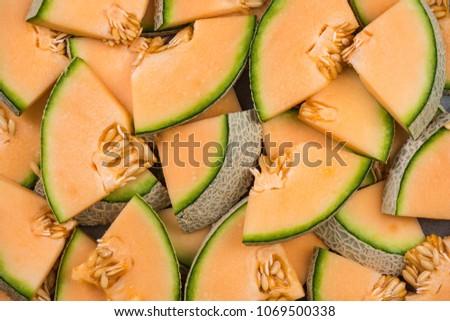 Cantaloupe melon slices, full frame food background.