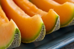 Cantaloupe melon slices sitting on blue platter in a row