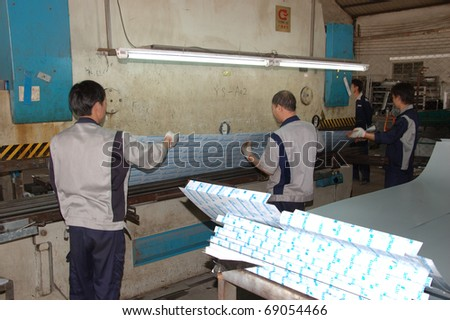 CANTON, CHINA - NOVEMBER 11: One of the biggest manufacturer of auto spray booths and generators in China. Chinese workers use machine to create aluminum profile on November 11, 2010 in Canton, China.